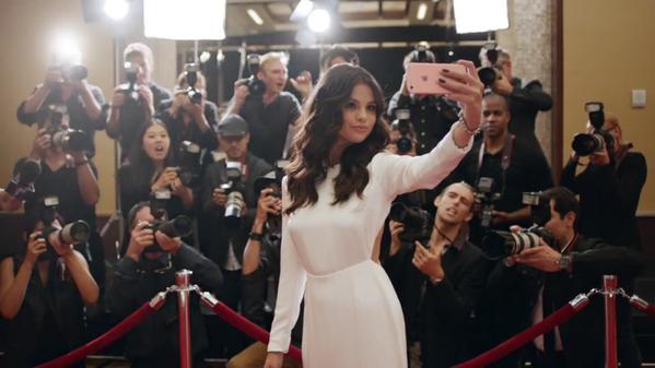 Selena Gomez si scatta un selfie sul red carpet con alle spalle i fotografi