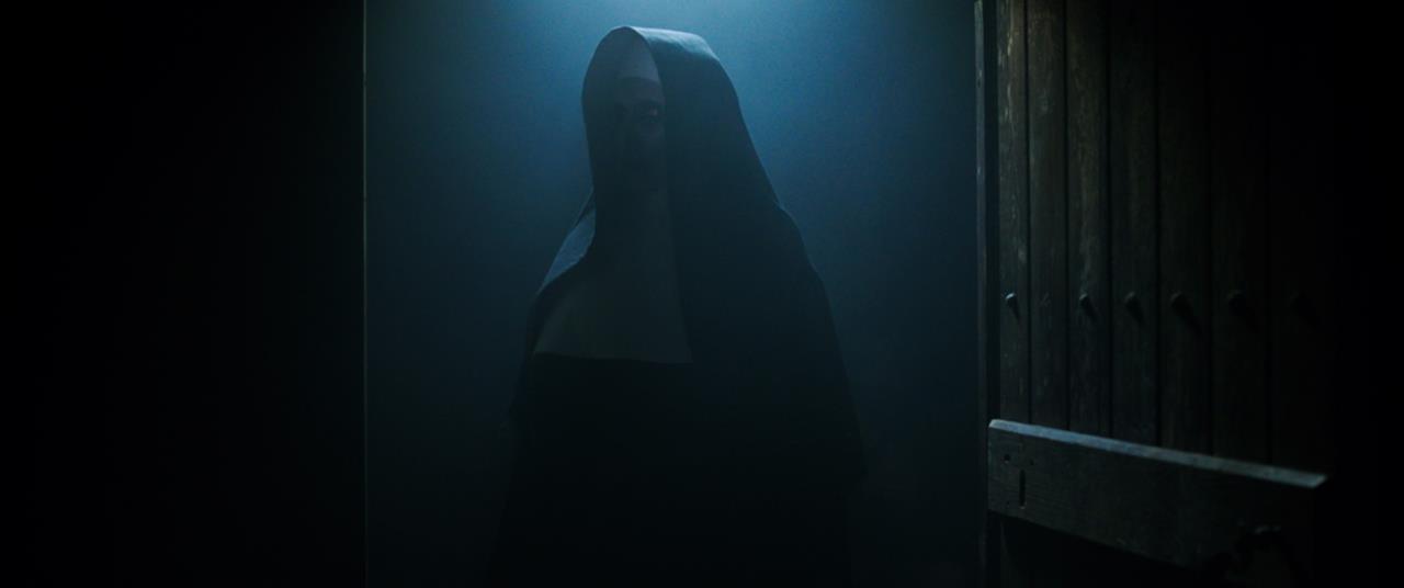 Valak, con le sembianze di una suora, al buio in una scena di The Nun