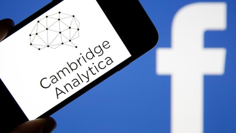 Primo piano del logo di Cambrige Analytica e sullo sfondo quello di Facebook