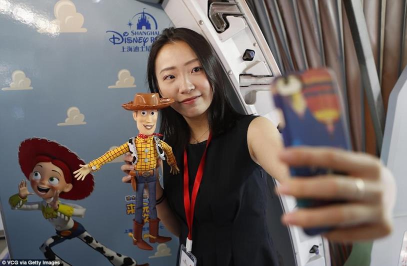 Aereo a tema Toy Story. una turista intenta a scattarsi un selfie mentre mostra la bambola di Woody