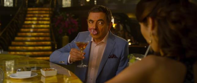 Rowan Atkinson con un ombrellino da cocktail nel naso