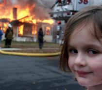 Una bambina davanti a una casa in fiamme