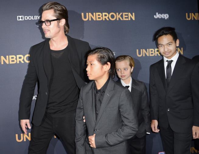 Primo piano di Brad Pitt con tre dei suoi figli
