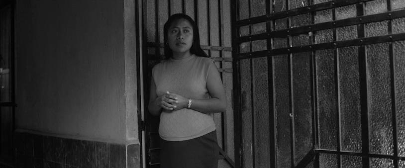 Yalitza Aparicio affacciata alla porta di casa in una scena del film Roma di Alfonso Cuarón