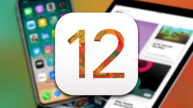 Primo piano del logo iOS 12 e sullo sfondo un iPhone e un iPad