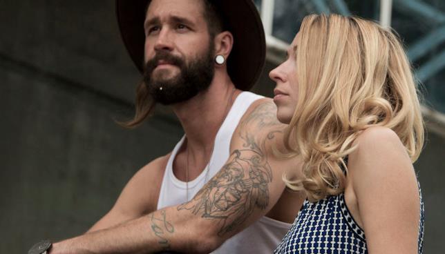Un uomo tatuato di profilo con un gioiello Krato Milano nella barba