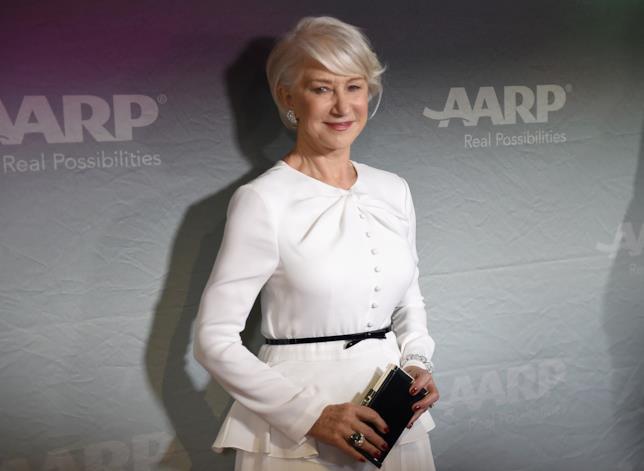 Hellen Mirren sul red carpet che regge la pochette e sorride