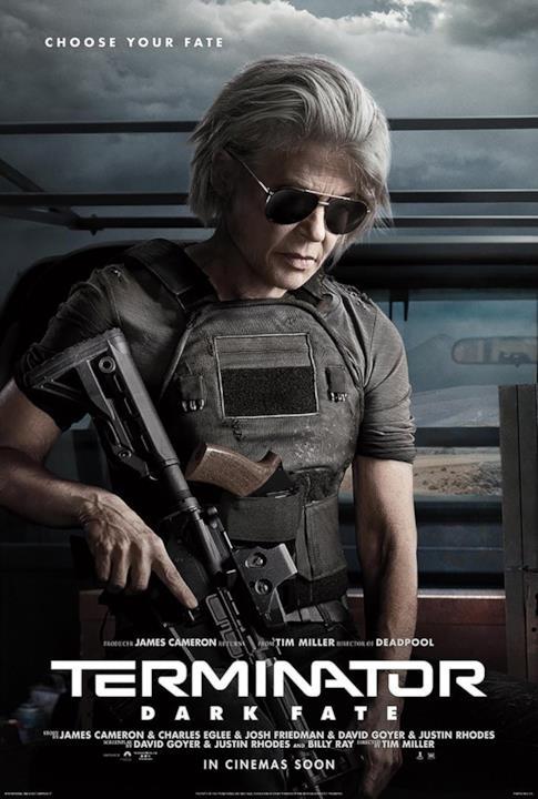 Linda Hamilton nel retro di un veicolo, indossa occhiali da sole scuri e impugna un fucile