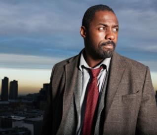Mezzobusto di Idris Elba con città sullo sfondo, all'alba
