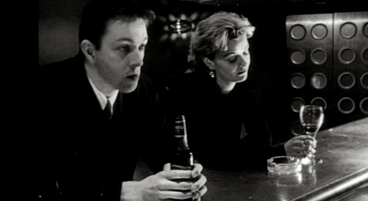 Lo scrittore e la bionda parlano al bancone del bar
