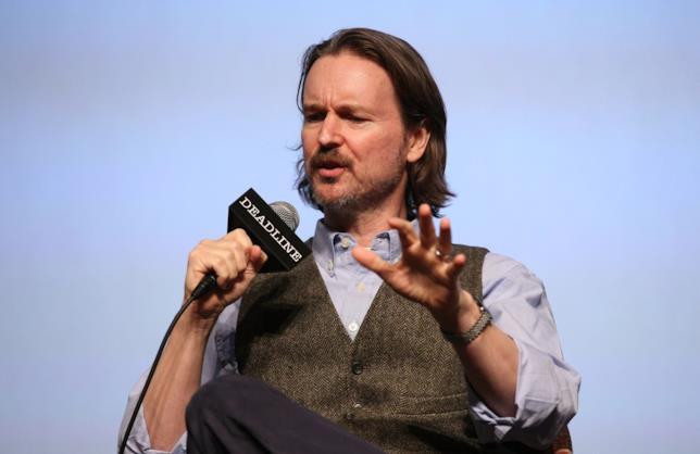 Un ritratto di Matt Reeves in gilet, camicia e microfono, mentre risponde alle domande di Deadline