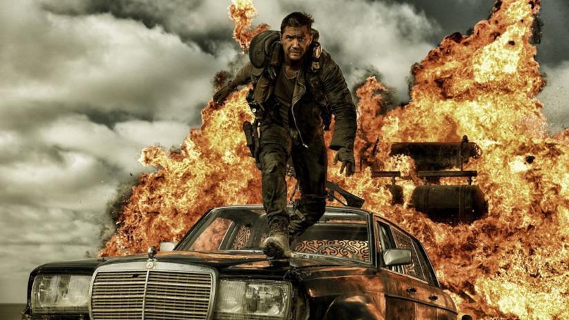 Tom Hardy nel ruolo di Max, mentre cammina su una auto in fiamme