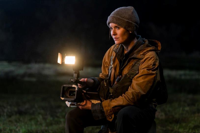 Maggie Grace di notte con una telecamera tra le mani, in un prato