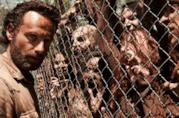 Una rete divide Rick Grimes da un gruppo di zombie