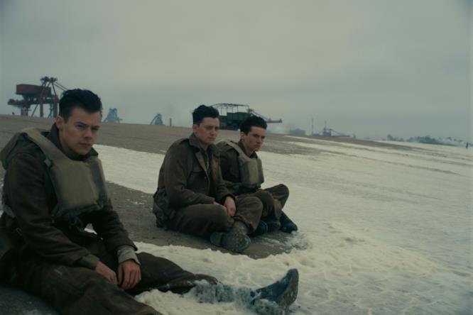 Tre militari aspettano sulla riva del mare