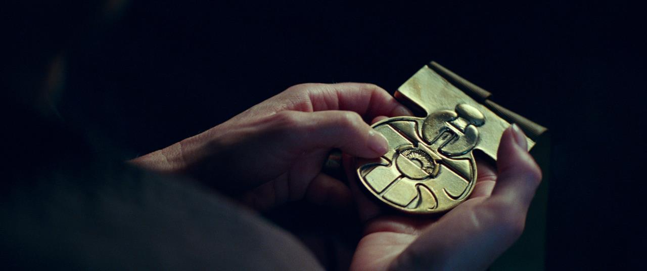 Carrie Fisher con la  medaglia di Han Solo fra le mani
