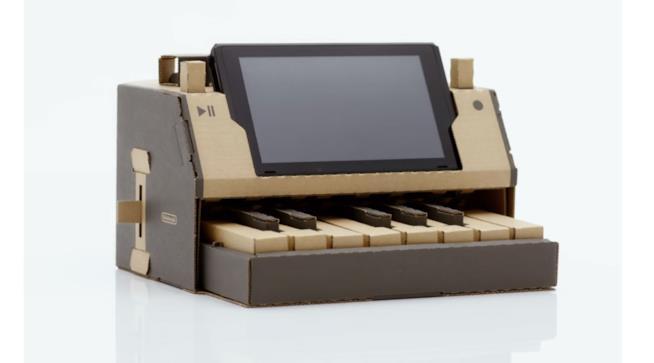 Primo piano di un pianoforte di cartone con la console Switch costruito con il kit di Nintendo Labo
