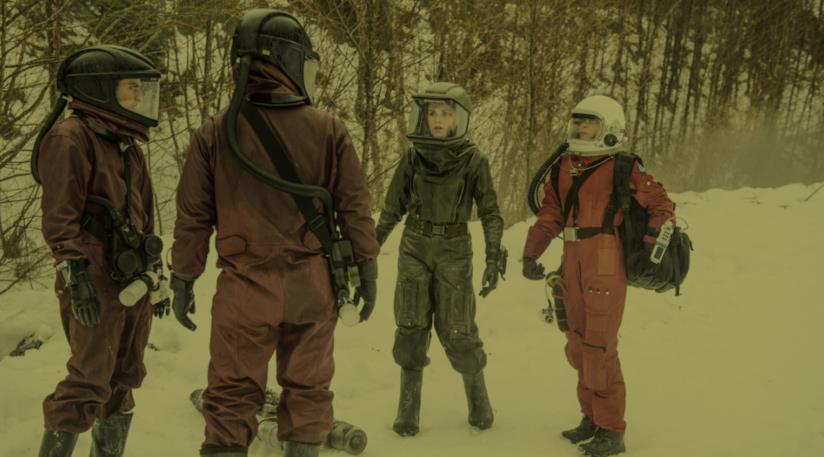 I protagonisti di The 100 con delle tute e dei caschi protettivi, circondati dalla neve