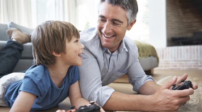Padre e figlio giocano con un console