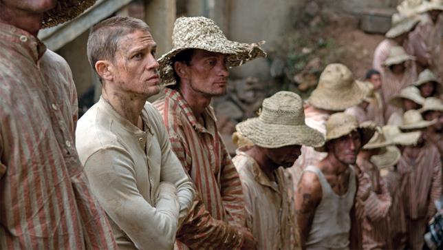 Charlie Hunnam con gli altri prigionieri in una scena del film