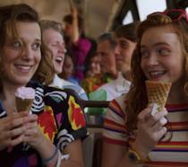 I personaggi di Undici e Max di Stranger Things su un bus, ridono e mangiano il gelato