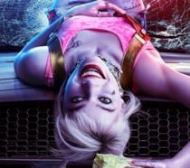 Margot Robbie, nei panni di Harley Quinn,  a testa in giù sul cofano di una auto