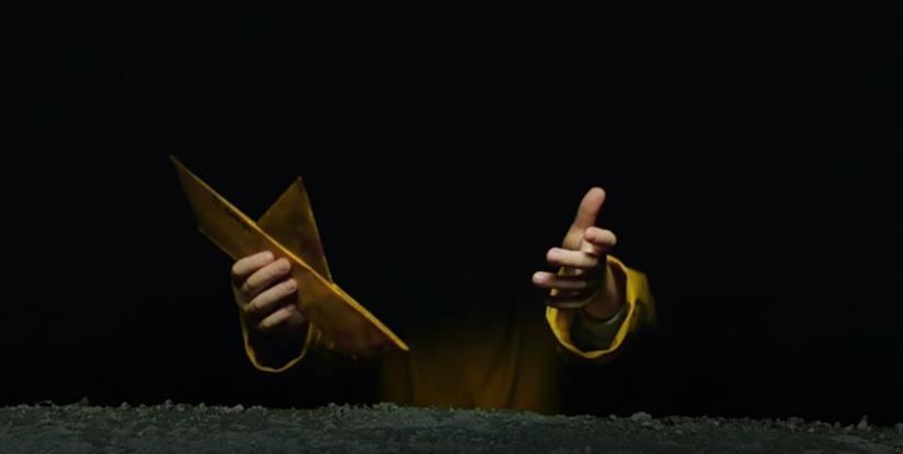 Barchetta e impermedabile giallo che emergono dal buio delle fogne