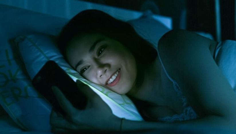 Una giovane utilizza lo smartphone al buio