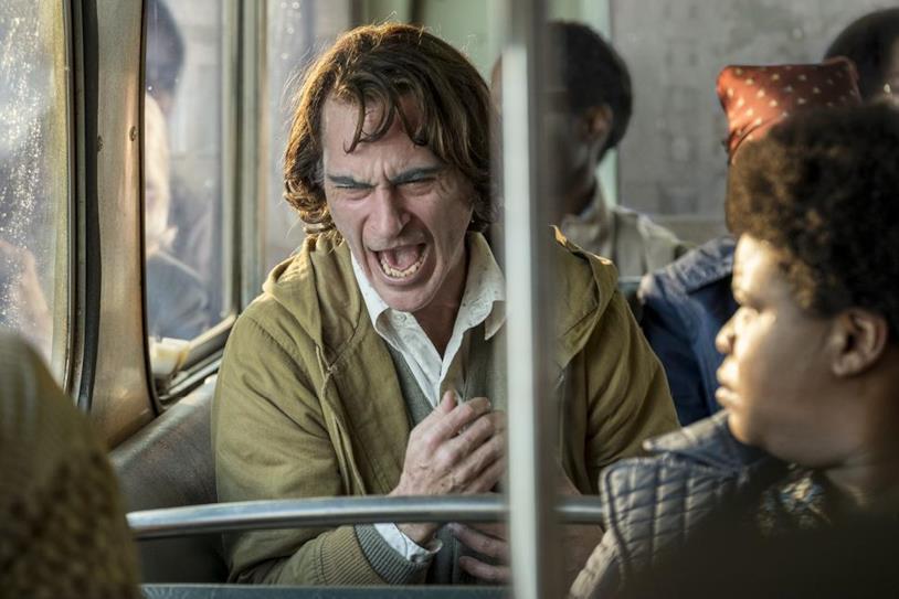Joaquin Phoenix seduto sull'autobus in una scena di Joker