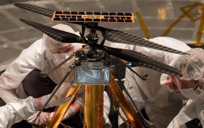 Due scienziati intenti a mettere a punto l'elicottero prima di una fase di test di volo