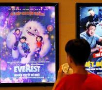 Ragazzo guarda le locandine dei film in un cinema