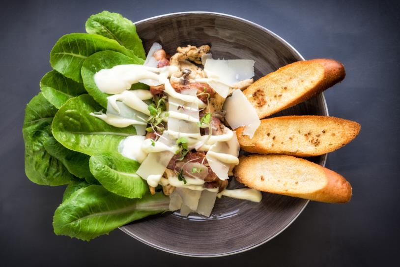 Primo piano di un'insalata Caesar con uova e crostini