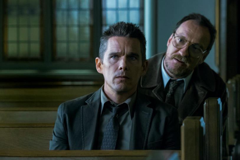 Lo psicologo Raines e il detective Bruce discutono seduti sulle panche della chiesa