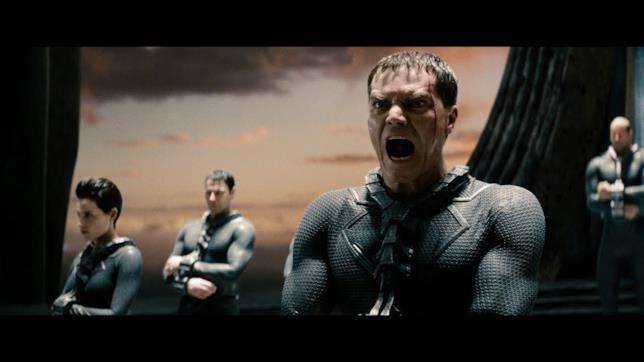 Mezzobusto di Michael Shannon urlante in tuta nera e altri personaggi sullo sfondo kryptoniano
