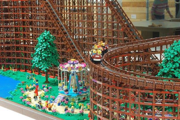 Dettagli della montagne russe di LEGO: alberi, un fiume e una giostra.