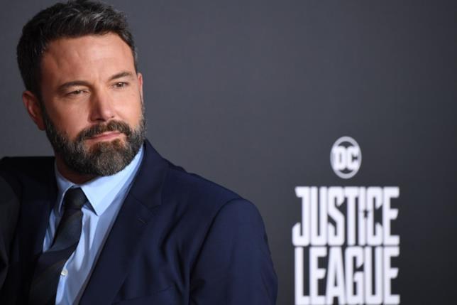 Ben Affleck davanti a logo della Justice League