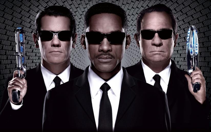Gli agenti di Men in Black in primo piano con gli occhiali scuri e le pistole