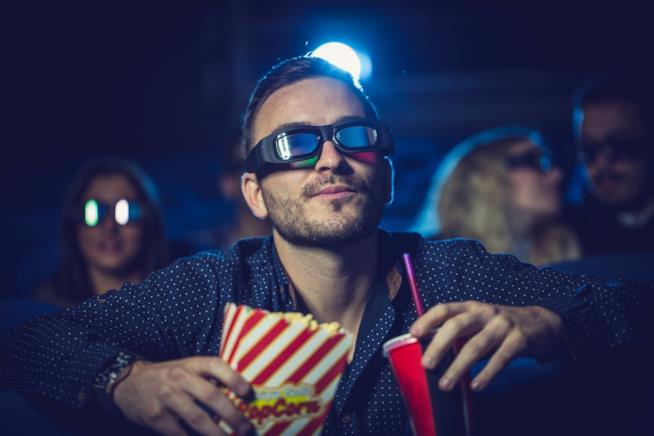 Uno spettatore al cinema con occhiali 3D e pop-corn
