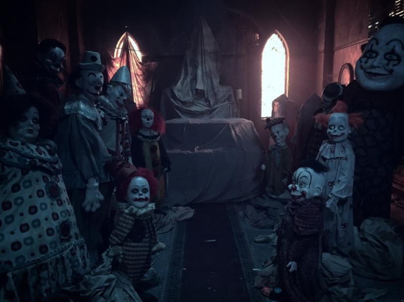 Il Pennywise di Tim Curry in una stanza piena di bambole dalle fattezze clownesche
