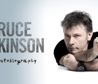 Bruce Dickinson in posa, con il dito indice alzato a puntare la grafica di un pulsante