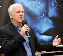 Mezza figura di James Cameron davanti alla locandina di Avatar