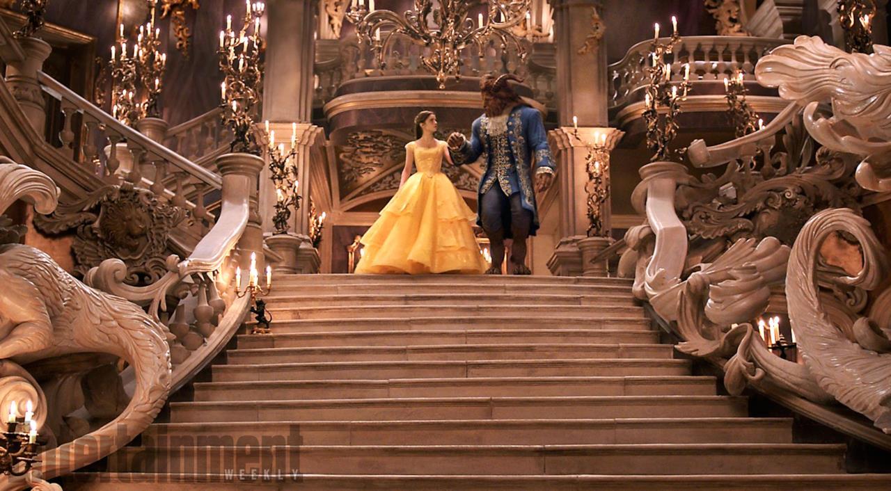 La Bestia offre il braccio a Belle mentre la coppia scende le scale della sala da ballo