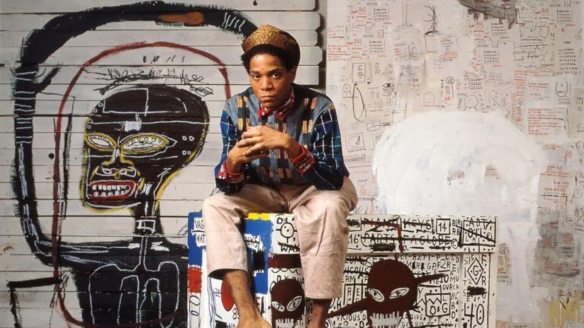 Jean-Michel Basquiat in un'immagine che lo ritrae davanti a una sua opera