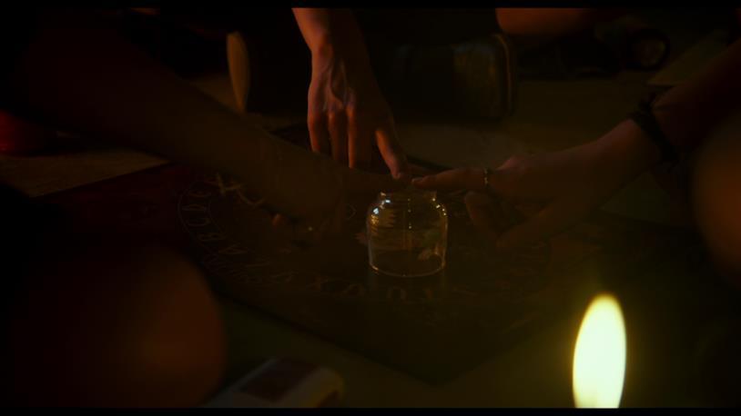 Le mani di Veronica, Rosa e Diana seguono il puntatore della tavoletta Ouija