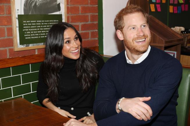 Harry e Meghan seduti a un tavolo