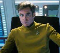 Mezzobusto di Chris Pine nell'uniforme del Capitano Kirk, seduto sulla poltrona dell'Enterprise