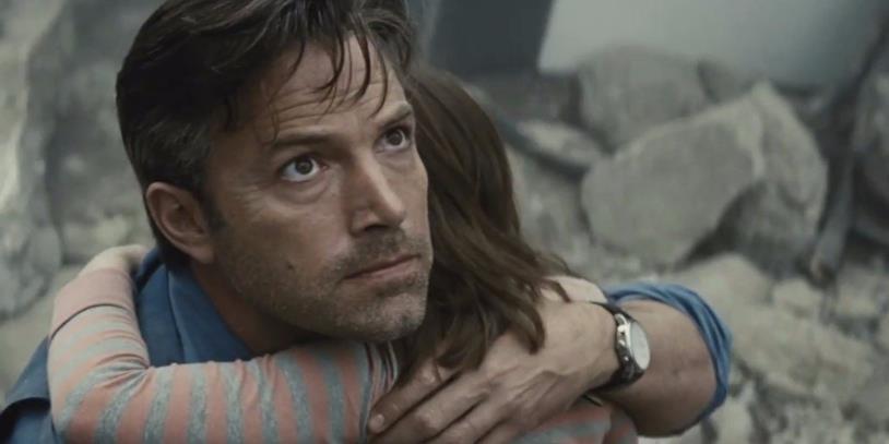 Primo piano di Ben Affleck che abbraccia una bambina, con macerie sullo sfondo