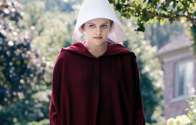 Difred (Elisabeth Moss) con mantello rosso e capello bianco