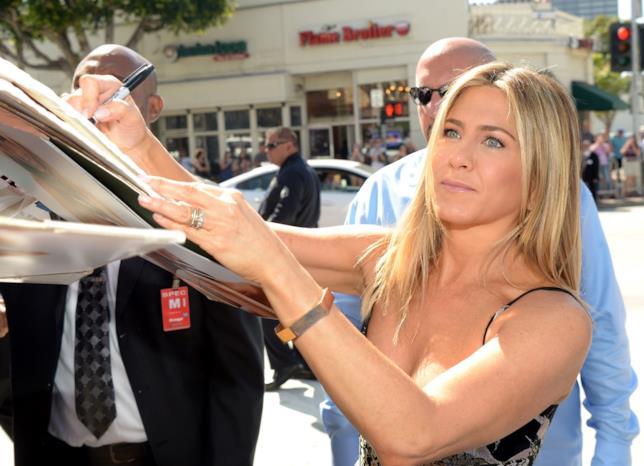 Primo piano di Jennifer Aniston intenta a firmare autografi