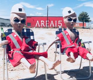 Due alieni di gomma con sullo sfondo la sede di Area 15.